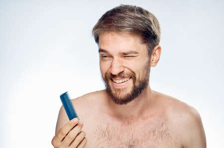 hair stylist: Young guy with a beard on a white isolated background holds a comb