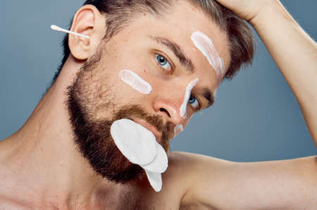 A young guy with a beard on a gray background, wadded disks, ear wand, cosmetic cream.