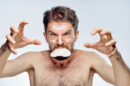 Young guy with a beard on a white isolated background, wadded disks, ear wax, cosmetic cream. Stock Photo