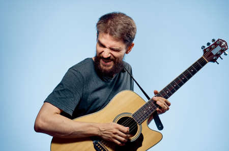 plucking: Young guy with a beard on a blue background holds a guitar.