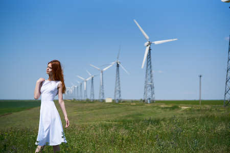female sexuality: Young beautiful woman in a white dress in a field near a windmill. Stock Photo