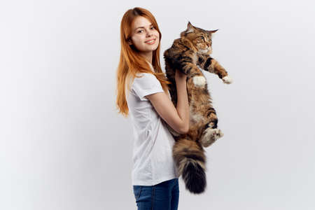 Young beautiful woman on a light background holds a cat, an allergy.
