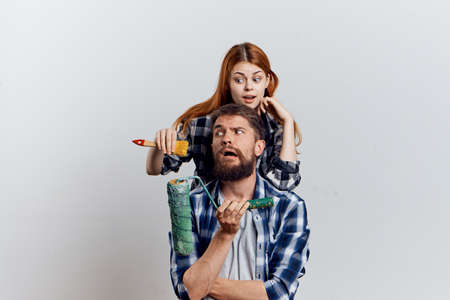 two persons only: Young beautiful woman with a guy with a beard on white isolated background, repair, construction tools. Stock Photo