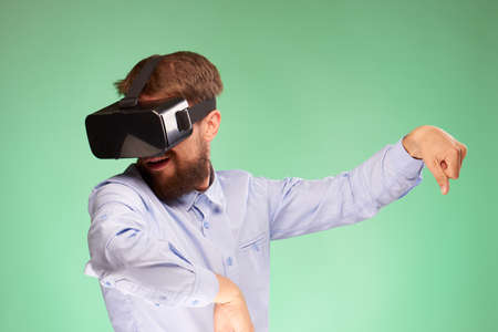handsfree telephone: A young guy with a beard on a green background in the eyes of virtual reality. Stock Photo