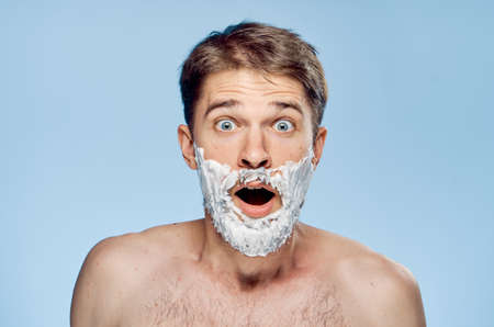 mirror image: Man with a beard on a gray background in shaving foam.