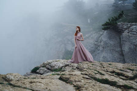 Young beautiful woman in a long pink dress is standing in the mountains in the fog. Stock Photo