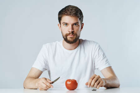 Vegetarian, diet, man with a beard on a white isolated background, nutrition, vegetables, vegetarianism.