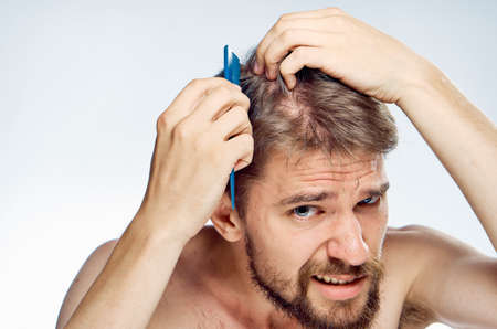 barber: Man with a beard on a white isolated background combs his hair. Stock Photo