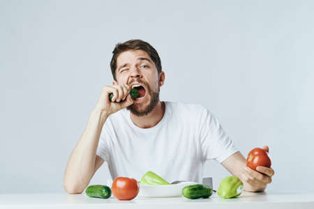 Mann mit einem Bart auf hellem Hintergrund, Gemüse, Diät, Vegetarismus, Vegetarier.