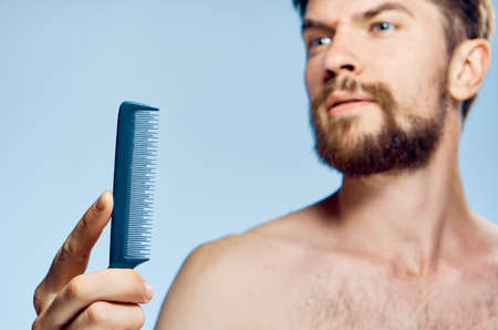 hair stylist: Man with a beard on a blue background holds a comb.