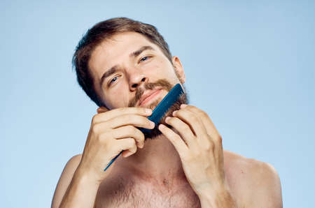 Man with a beard on a blue background combing.