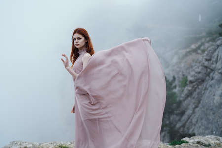 Beautiful young woman in a long dress on a cliff of a mountain in the fog.