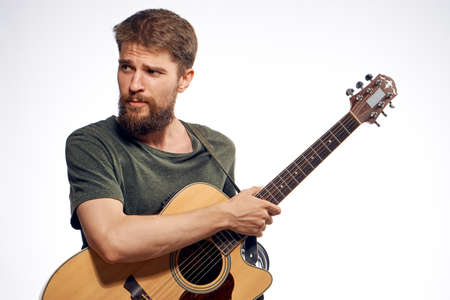 plucking: Man with a beard on a white isolated background holds a guitar, play, musical instruments, music, strings. Stock Photo