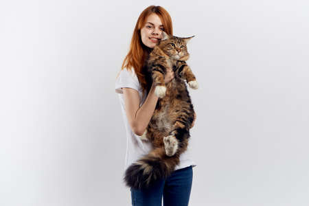 Beautiful young woman on a light background holds a cat, an allergy.