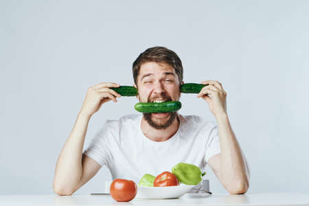 Man with a beard on a light background, vegetables, diet, vegetarianism, vegetarian. Stock Photo