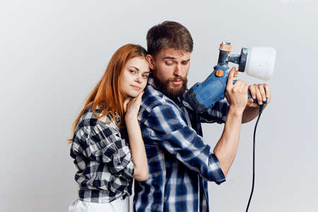 Beautiful young woman and man with a beard on a light background, repair, construction tools.