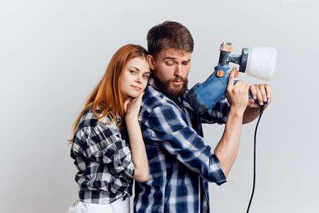 Piękna młoda kobieta i mężczyzna z brodą na jasnym tle, naprawy, narzędzia budowlane.
