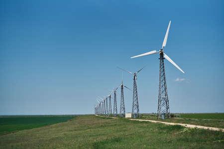 Windmills in the field, summer, sun, grass, sky.