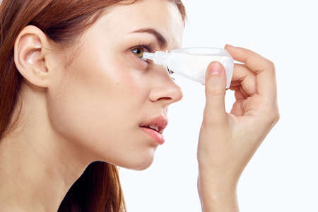 Young beautiful woman on white isolated background dripping in the eyes eye drops. Stock Photo