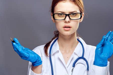 Joven y bella mujer sobre un fondo gris en caucho guantes médicos, medicina, médico, médico. Foto de archivo