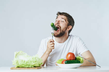 Man with a beard on a light background eating vegetables, cucumber, lettuce, tomato, diet, vegetarianism, vegetarian.