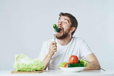 Mann mit einem Bart auf einem hellen Hintergrund Gemüse, Gurke, Salat, Tomate, Diät, Vegetarismus, Vegetarier essen.
