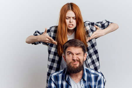 Man with a beard on a light background with a young beautiful woman, emotions.