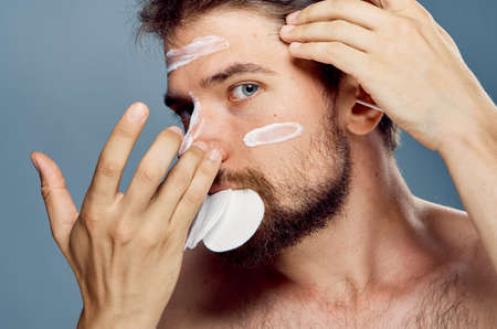 A man with a beard on a gray background applies cosmetic face cream, cotton pads. Stock Photo