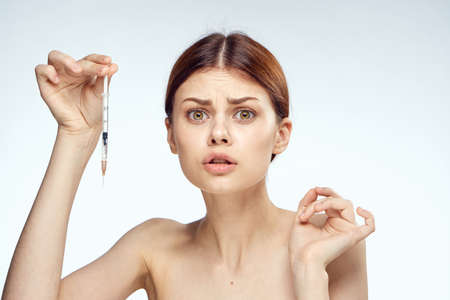 Young beautiful woman on white isolated background holds a syringe, plastic, medicine, health, beauty.