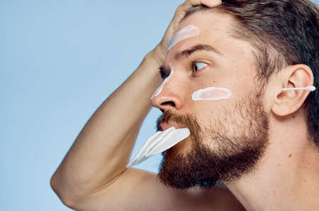 A man with a beard on a blue background in a cosmetic cream holds in his mouth wadded disks, ear wands.