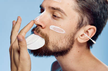 A man with a beard on a blue background holds wadded disks in his mouth, cosmetic cream, ear wand.