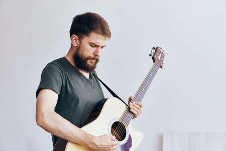 plucking: Man with a beard on a white isolated background playing a guitar, musical instruments.