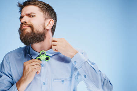 Man with a beard on a blue background holds a spinner, toy, entertainment.