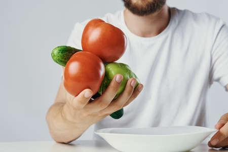 Man holds vegetables in his hand, vegetarian, diet.