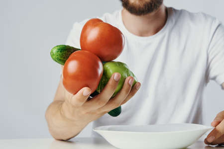 Man holds vegetables in his hand, vegetarian, diet.