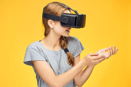 Woman in virtual reality glasses plays on a yellow background.