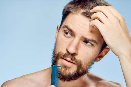 A man with a beard on a blue background holds a comb, a hairdo.