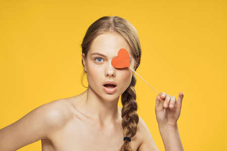 Woman attached a paper accessory heart to the eye on a yellow background.