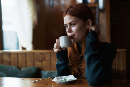 Woman drinks coffee in a cafe, rest. Stock Photo