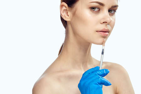 Young beautiful woman on white isolated background in rubber gloves holds syringe, portrait, plastic surgery, medicine.