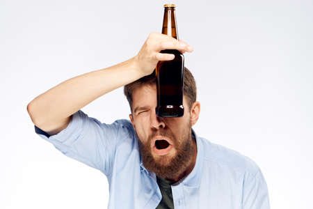 A man with a beard holds a bottle of beer near his eye a second eye closed on a light background. Stock Photo