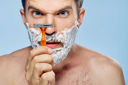 A man with a machine and with a shaving foam on his beard on a blue background Фото со стока