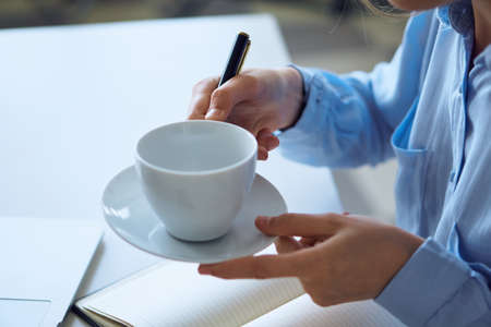 Woman holding a mug, white table, notebook, organizer. Stock Photo