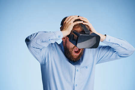 handsfree telephone: Man with a beard on a blue background with glasses of virtual reality, entertainment.