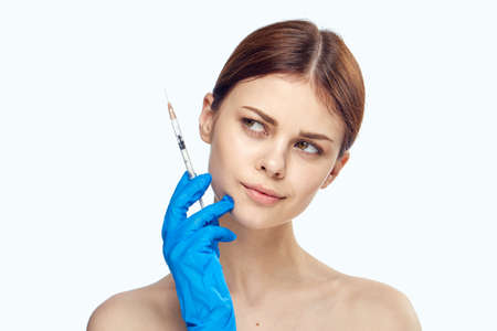 Young beautiful woman on white isolated background in rubber gloves holds syringe, plastic surgery, medicine.