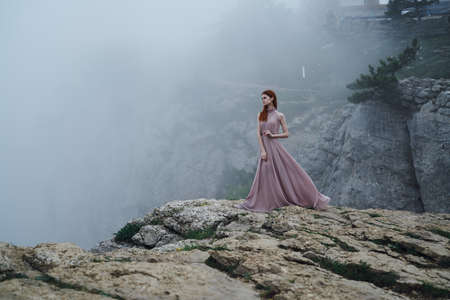 Young beautiful woman in a long pink dress on a cliff of a mountain in the fog. Stock Photo