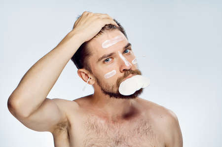 Man with a beard on a white isolated background, wadded disks, cosmetic cream, ear wand. Stock Photo