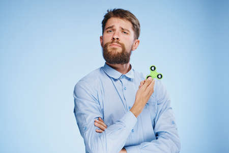 cool gadget: Man with a beard on a blue background in a shirt holds a spinner spinner, entertainment.