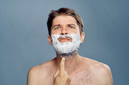 mirror image: Man with a beard on a gray background in shaving foam, emotions, portrait.
