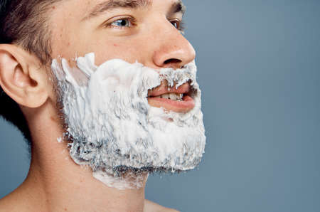 mirror image: Man with a beard on a gray background in shaving foam, portrait. Stock Photo